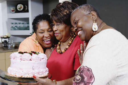 Three middle-aged African women holding cake Stock Photo - 16091513