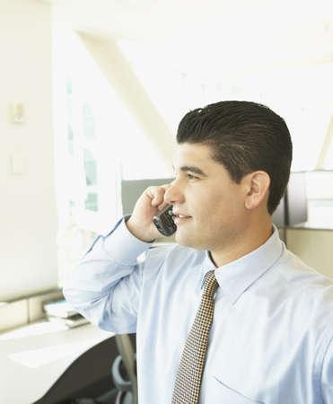 cubical: Hispanic businessman using telephone LANG_EVOIMAGES