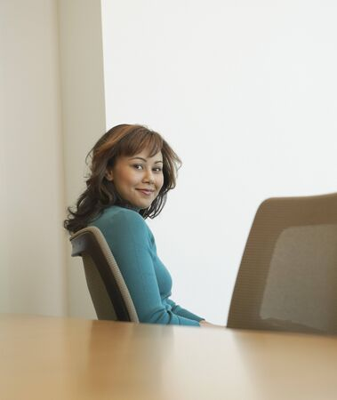 Businesswoman sitting at conference table Stock Photo - 16091540