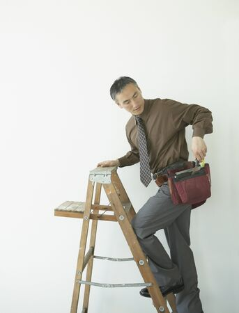 scaling ladder: Asian businessman with toolbelt climbing up ladder