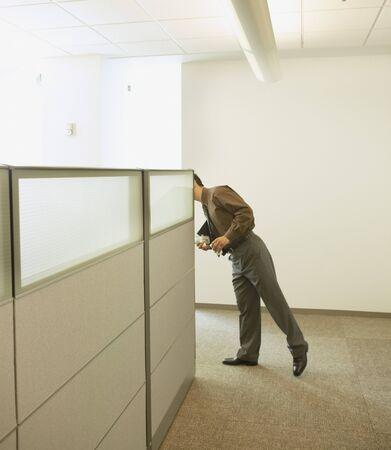 cubical: Businessman peeking around cubicle wall