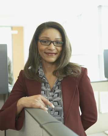 cubical: African businesswoman smiling in cubicle LANG_EVOIMAGES