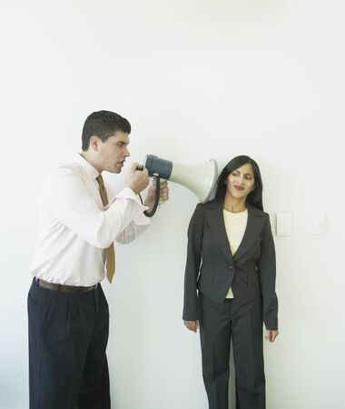 Businessman with megaphone yelling at businesswoman Stock Photo - 16091555