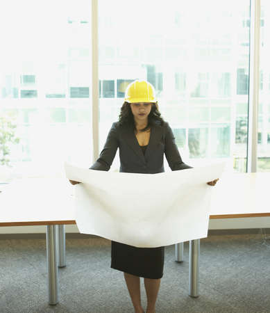 hilarity: Businesswoman wearing hard had and looking at blueprints