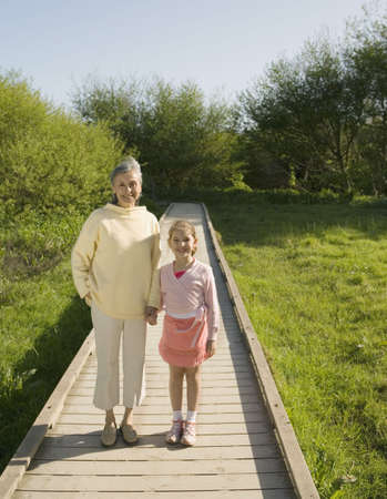 gramma: Grandmother and granddaughter holding hands outdoors
