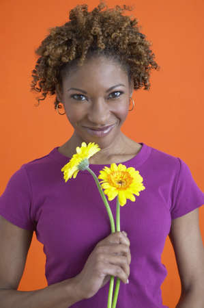 African woman smiling and holding flowers Stock Photo - 16091575
