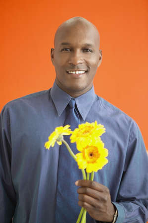 holding close: African man holding flowers LANG_EVOIMAGES