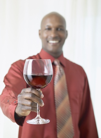 African man holding glass of red wine