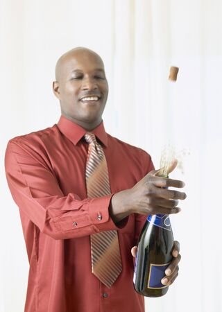 popping the cork: African man popping cork on champagne LANG_EVOIMAGES