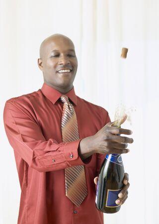 African man popping cork on champagne Standard-Bild