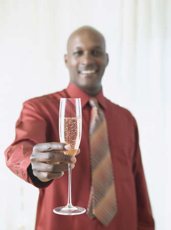 African man holding up glass of champagne Stock Photo - 16091581