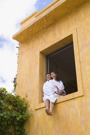 Couple in bathrobes sitting in window Stock Photo - 16091592