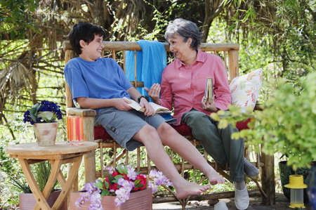 gaiety: Hispanic grandmother and grandson reading outdoors LANG_EVOIMAGES