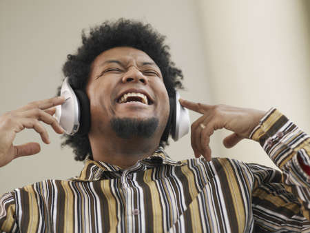 low spirited: African man listening to music on headphones