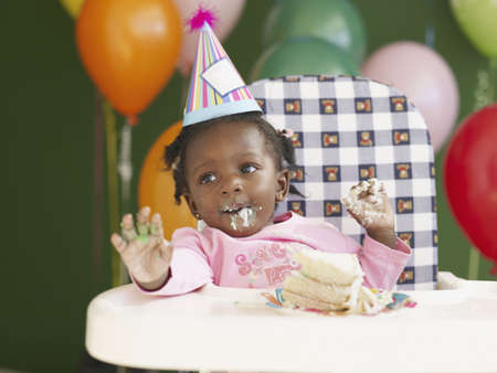 african america: African baby in high chair wearing party hat and eating cake LANG_EVOIMAGES