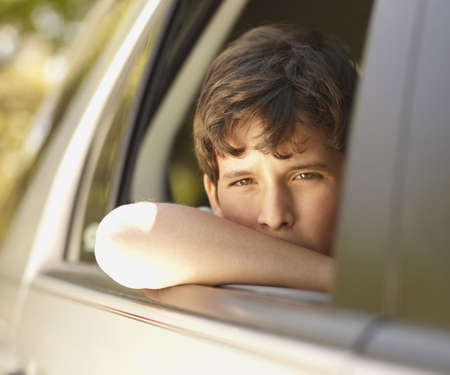tiring: Boy leaning out of car window
