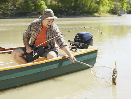 Man in small boat catching fish in net Stock Photo - 16091617