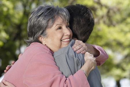 Hispanic grandmother hugging grandson