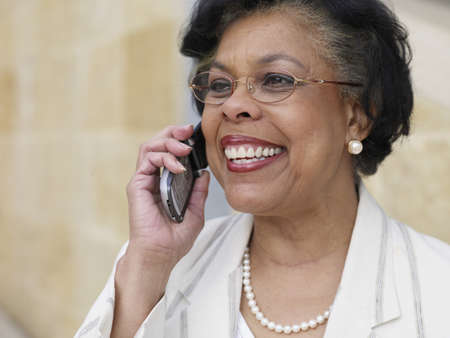 african american woman business: Senior African businesswoman using cell phone outdoors