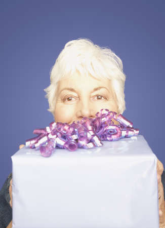 mischeif: Studio shot of senior woman with gift