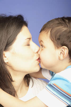 Studio shot of mother kissing young son Stock Photo - 16091648