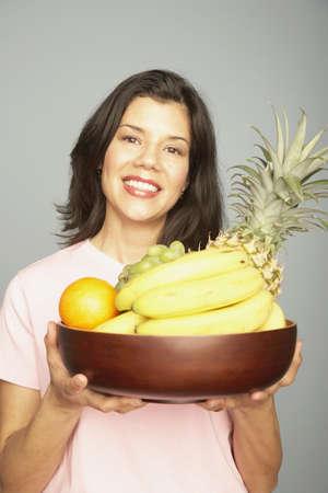 Studio shot of woman holding bowl of fruit Stock Photo - 16091658