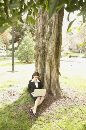 well beings: Businesswoman using laptop under tree