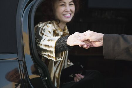 departing: Asian woman being helped out of luxury car