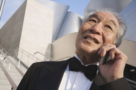 acknowledging: Senior Asian man in tuxedo using cell phone