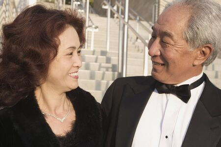 'evening wear': Senior Asian couple in evening wear outdoors LANG_EVOIMAGES