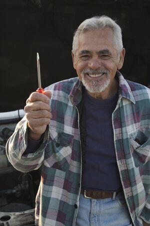 Senior man smiling and holding screwdriver Stock Photo
