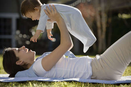 kinfolk: Hispanic mother lying on the grass holding baby above her