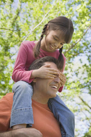 fathering: Hispanic father with daughter on shoulders