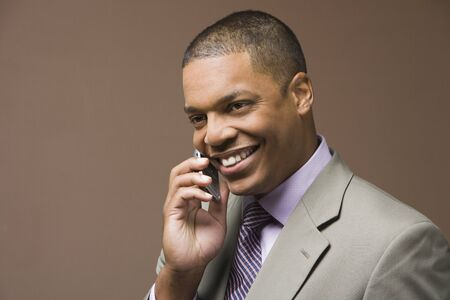 Studio shot of African businessman using cell phone Stock Photo - 16091716