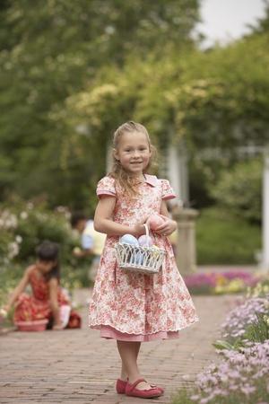 easter egg hunt: Young girl with Easter basket in garden LANG_EVOIMAGES