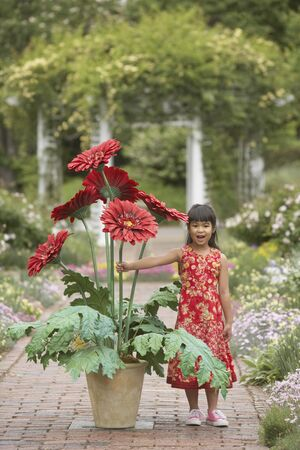 Asian girl in garden with giant potted plant Stock Photo - 16091719