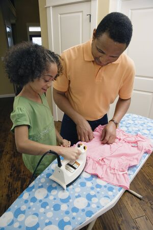 helpful: African father and daughter ironing