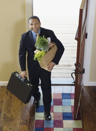 homecoming: African businessman arriving at home with groceries