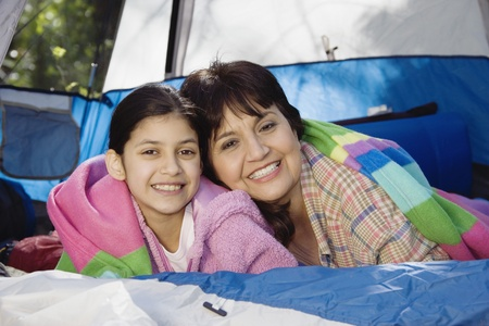babyboomer: Grandmother and granddaughter laying in tent smiling LANG_EVOIMAGES