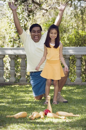 babyboomer: Indian father and daughter playing lawn bowling