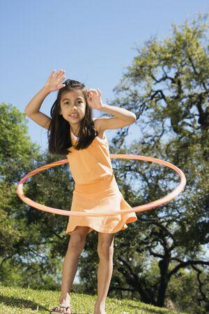 Hispanic girl playing with hula hoop outdoors Stock Photo - 16091739