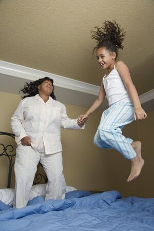 misbehaving: African mother and daughter jumping on bed LANG_EVOIMAGES