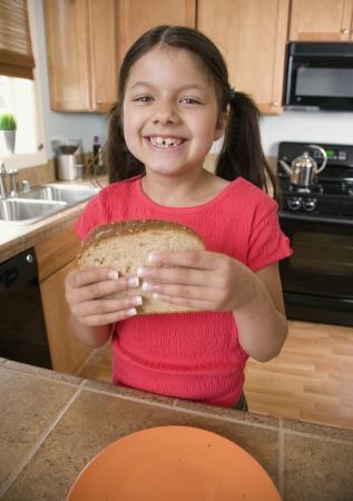 concluding: Hispanic girl eating sandwich in kitchen LANG_EVOIMAGES