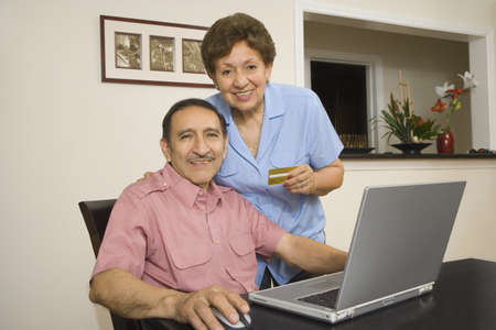 old furniture: Senior Hispanic couple with credit card and laptop