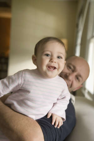 babyboomer: Father holding smiling baby on sofa