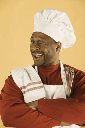 bathtowel: Studio shot of African man in chef outfit winking