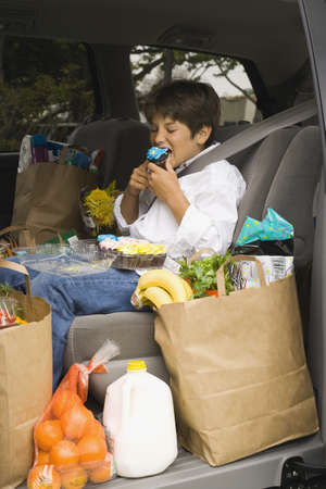 misbehaving: Boy sitting in backseat of car eating with groceries