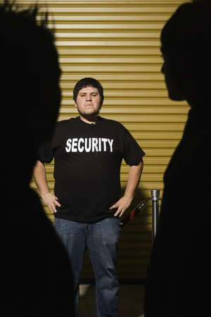 vigilant: Man wearing Security shirt with hands on hips