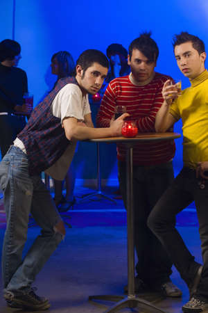 peruvian ethnicity: Three young men with cocktails at nightclub table
