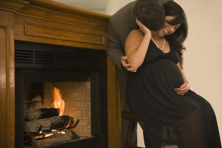 Pregnant couple in fancy clothing hugging next to fireplace Stock Photo - 16091797